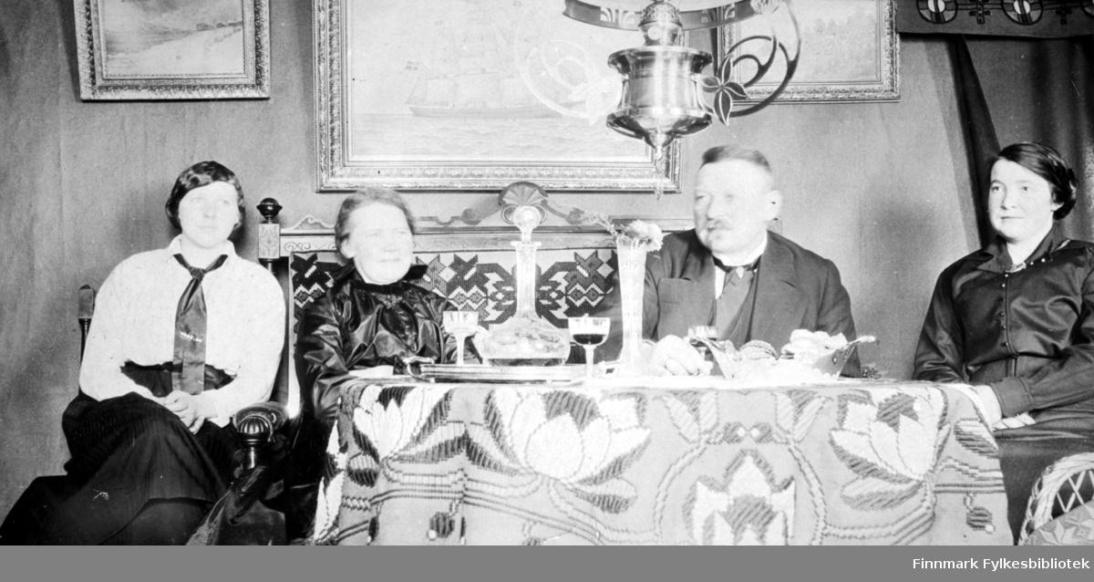 Fire personer sitter ved et bord. Mannen til venstre har en hvit/lys skjorte med slips og mørke bukser. Damen ved siden av han er Kirsten Buck. Hun har en mørk kjole. Mannen til høyre for henne er ektemannen Arthur Buck. Han har en ganske mørk dress med hvit skjorte og slips. Damen helt til høyre har en mørk kjole på seg. Det runde bordet foran dem har en mønstret duk og en karafel står oppå. En blomstervase, flere små glass og et fat/kurv står også på bordet. Bak dem henger et stort maleri med en seilskute og mindre bilder/maleri henger på hver side. Nedre del av en lysekrone ses midt på bildet. Sofaen har en høy rygg med mønster og utskjæringer. Gardinbrett med brede kapper henger over vinduet til høyre.