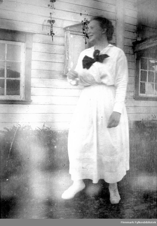 En dame står foran et hus. Hun har hvitt skjørt, hvit bluse og lyse sko på seg. En stor, sort sløyfe er knytt i halsen. Bakken hun står på er gressdekt og en liten/lav rad med planter står inntil husveggen. Huset har liggende panel og to sprossevinduer ses på bildet. En oppslagstavle henger på veggen mellom vinduene.