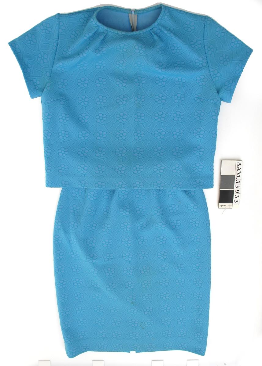 Kjole av turkis stoff. Todelt, med to ulike overdeler, en med korte, en med lange ermer. Etikett på langermet overdel.