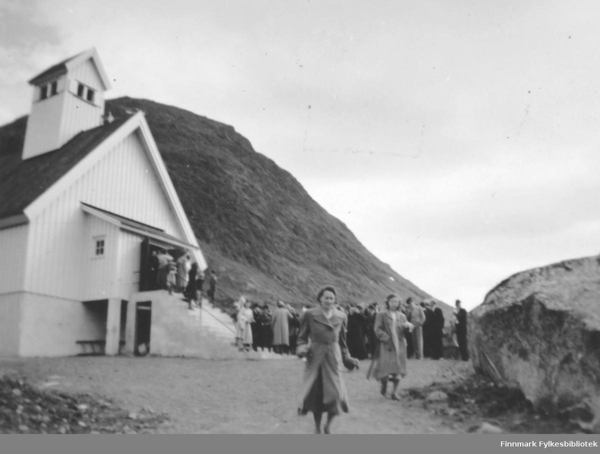 Mange mennesker utenfor Bergsfjord kirke ved innvielsen av den. Det står en del mennesker på kirketrappa og enda flere foran kirka. To damer i ganske lys kåper kommer gående ned kirkebakken mot kamera. Kirka har hvitt, stående panel. På røstveggen ser et lite tilbygg/vindfang med skrått tak, et lite sprossevindu og en lang trapp går fra bakkenivå og opp til inngangen. En stige ligger langs grunnmuren, under vindfanget. Kirketårnet har to to-delte vinduer på hver side. Alle delene på kirka, hovedbygget, vindfanget og tårnet har hvite vindski-bord. Kirkebakken har grusdekke og en stor stein ses helt til høyre på bildet. Bak kirka står et stort fjell, muligens Kollaren.