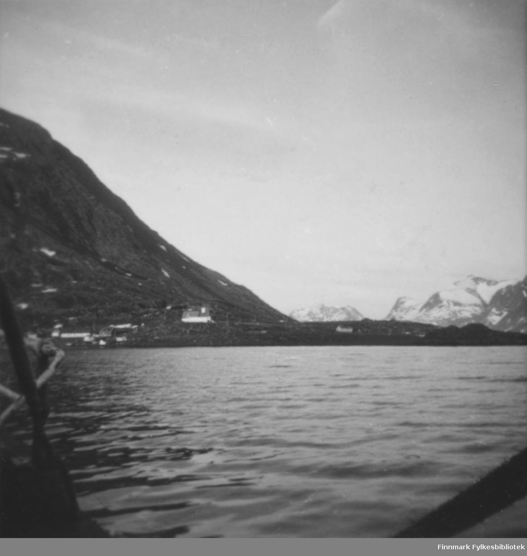 En ganske stille fjord, muligens Bergsfjord en sen vårdag. Et høyt fjell med en bratt fjellside og et nes stikkende ut i sjøen. Noen spredte snøflekker ligger i terrenget. Flere bygninger ligger i strandkanten og litt til venstre på bildet ligger en bygning som sannsynligvis er en kirke. Flere bygninger kan ses på neset. I bakgrunnen ses høye, delvis snødekte fjell. Rekka på en båt ses nede til høyre på bildet. Noe som kan være et fiskegarn henger på venstre siden.