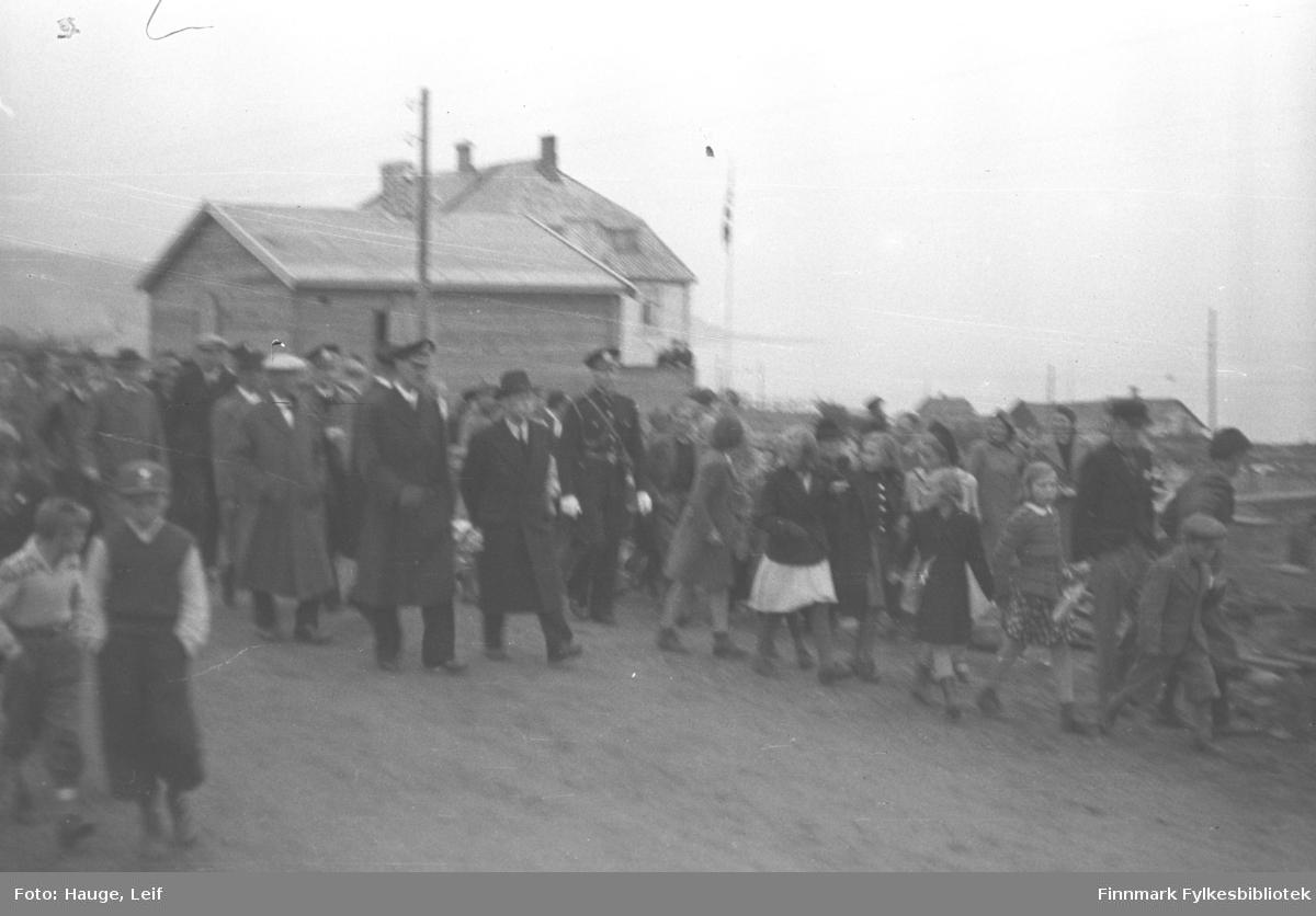 Mye folk står langs veien og ser på mens Kong Haakon og fylkesmann Gabrielsen med følge spaserer. Bygningen i bakgrunnen er kysthospitalet.