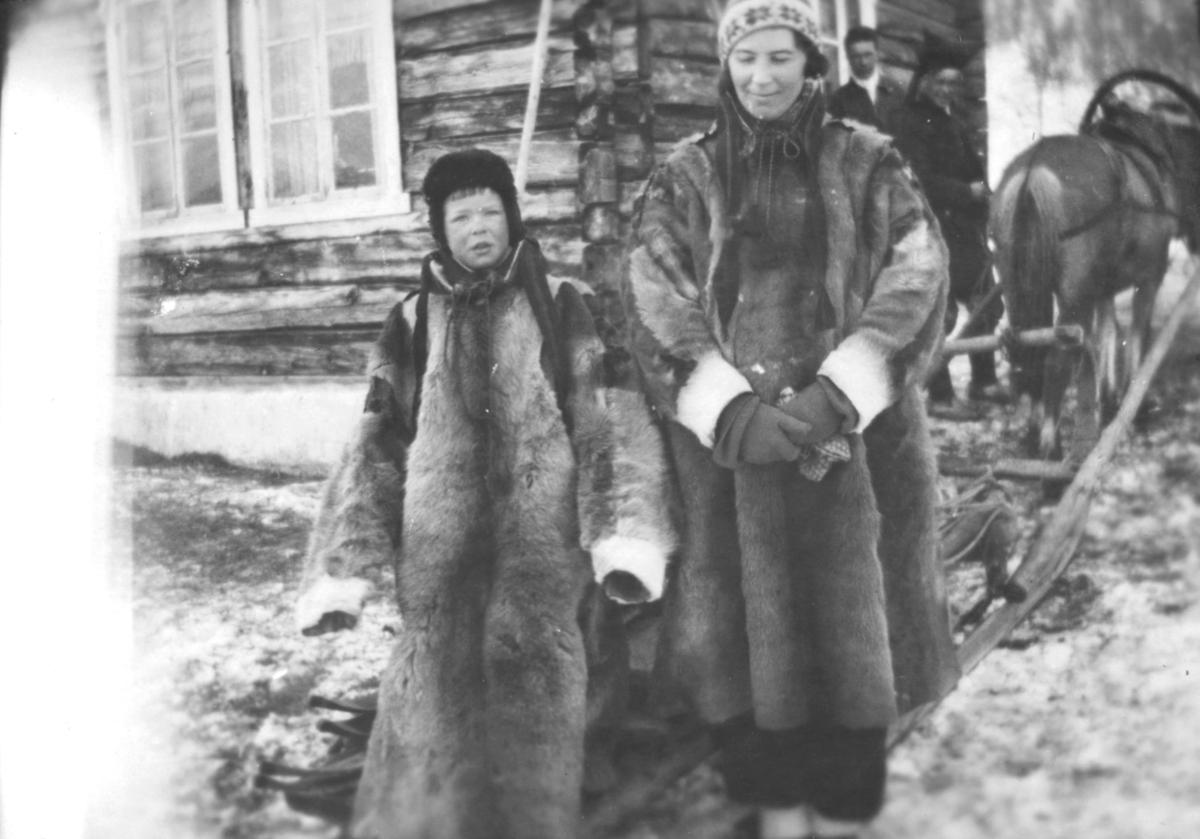 Tor Hauge, og moren Alfrida Hauge f. Amundsen, i lånte pesker. De står foran en tømmerbygning. I bakgrunnen står to menn, ved siden av en hest. Hesten er spent foran en slede. Det ligger snø på bakken