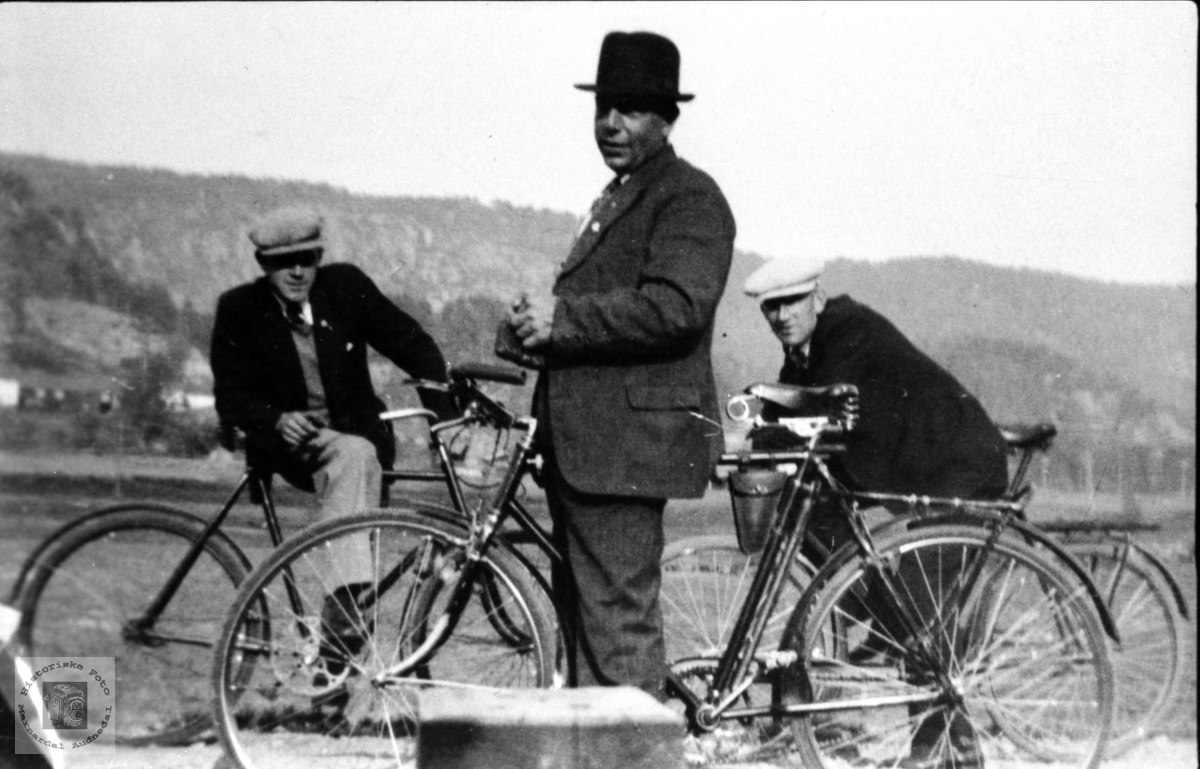 Tre menn med sykler på Laudal.