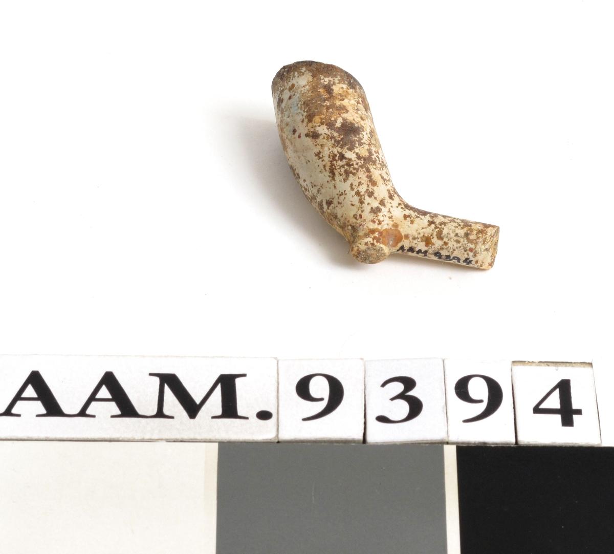 Krittpipehode,  engelsk type.  Langstrakt smalt hode  m. hæl uten bevart stempel. Bit av skaft bevart ved skaftfestet.   Lengde i alt 5,7 cm.