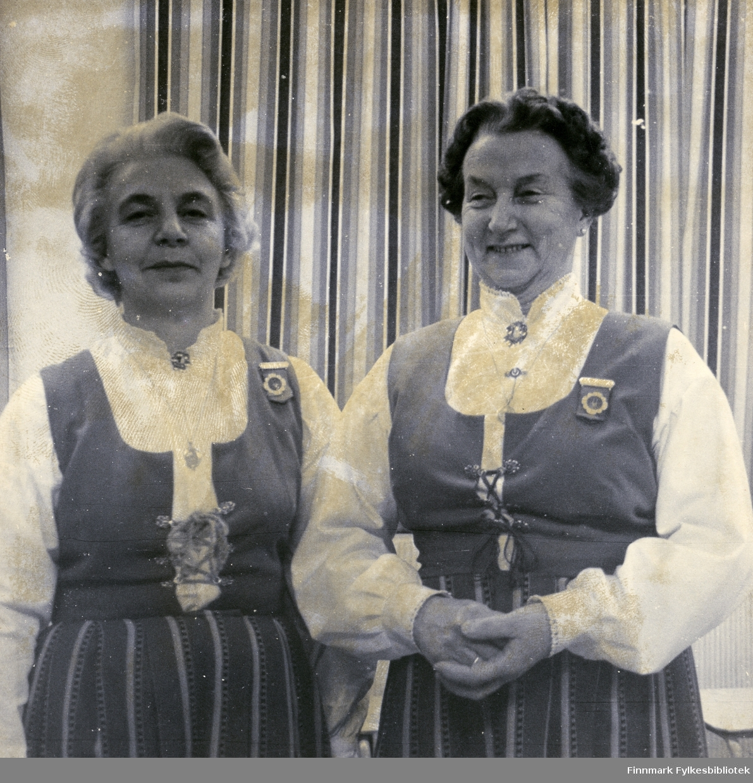 Borghild Dahl Løkting og Klara Pettersen (f. Pedersen) poserer sammen. De to var de som var med og startet Vadsø damekor 16.12.1946. Bildet er trolig tatt på 70/80-tallet. Kvinnene har på seg bunad, smykker og brosjer. Bak dem kan man se en gardin.