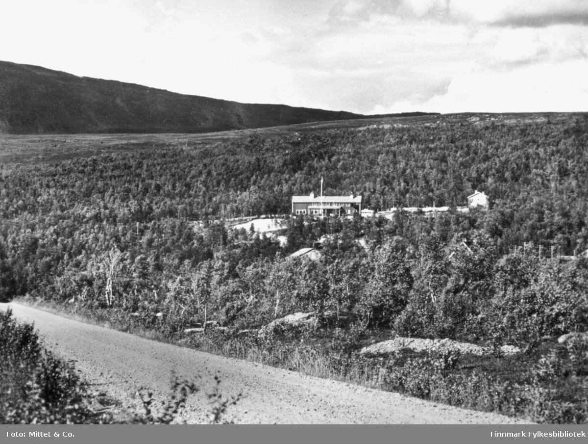 På bildet kan man se en bygning som er Skaidi gjestgiveri.Gjestgiveriet er omringet av skog og i bakgrunnen kan man se fjell.