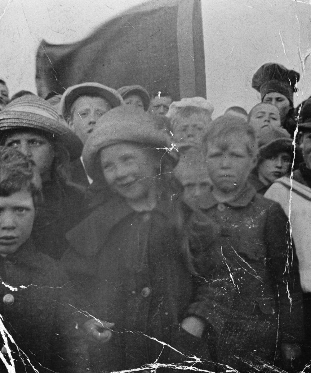Gruppebilde av søndagsskolebarn i Berlevåg tatt på utflukt til Skånsvikdalen. I bakgrunnen et flagg.  Fra venstre: Arne Gjæver Pedersen, Anna Sivertsen med stråhatt, Rolf Hansen ( delvis skjult i bakgrunnen), Ruth Lein med hatt og kåpe med stor krave og store knapper ( midt på bildet ), Birger Gjæver pedersen, Olaug Gjæver Pedersen, Olav Olsen ( Kjølnes i matrosdress). Det er ca 15 stk på bildet.