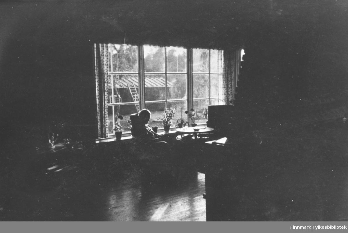 En kvinne sitter ved vinduet i et stort tømmerhus  i Petsamo / Petsjenga