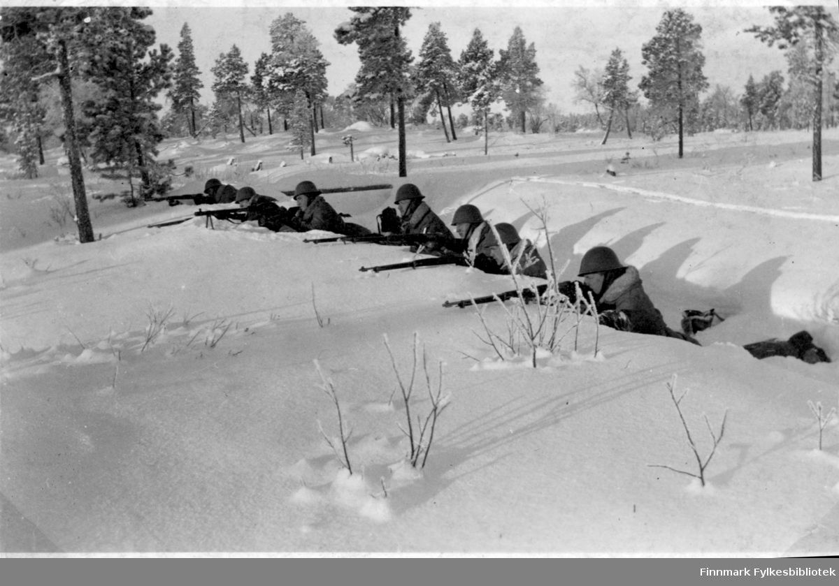 Soldater har øvelse i snøen, flere soldater ligger i skyttergraven og sikter med gevær.  Grensevakt, garnisonen i Sør-Varanger