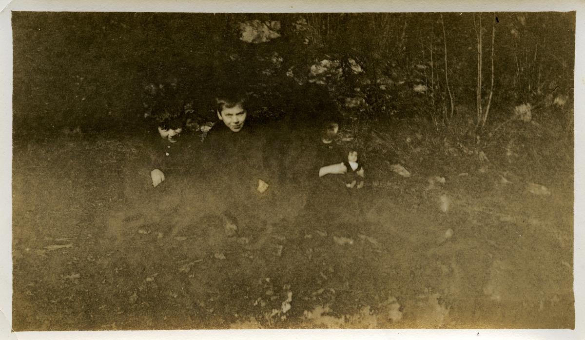 Tre barn sitter ute og poserer for et fotografi på ukjent sted. To gutter sitter kledd i jakke og bukse, og en jente sitter til høyre og holder på en dukke. Rundt barna kan man se stein og trær.