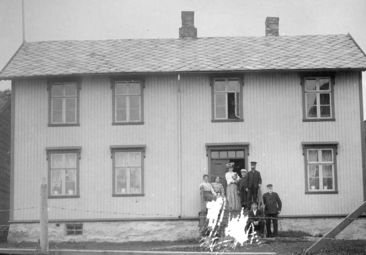 Skolen på Loppa. Lærerbolig i første etasje og klasserom i andre. Foran huset står en gruppe ukjente folk.