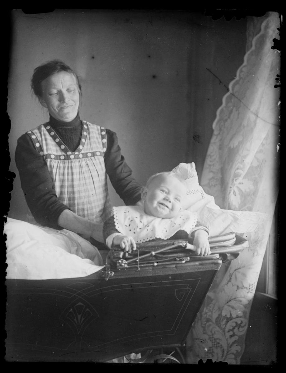 Et spedbarn sitter i vogna sitt at med vinduet inne i et rum og smiler. En kvinne står ved sidan av og støtter babyen under armene. Hunhar et stripet forklær på seg. Det henger en lang gardin ved vinduet.