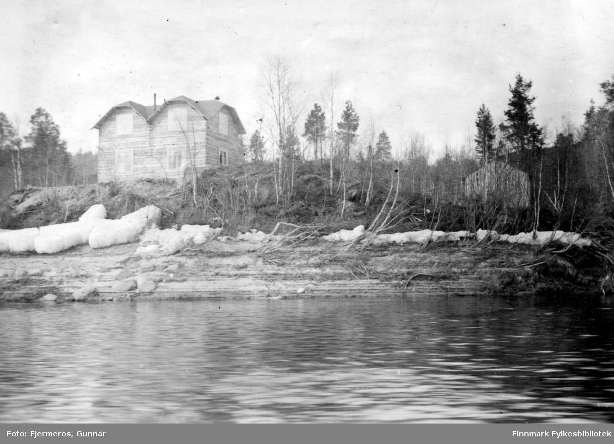 Et stort hus med valmet tak bygd på en liten høyde rett ovenfor vannkanten. Stedet er ukjent, men bildet er tatt i 1947.