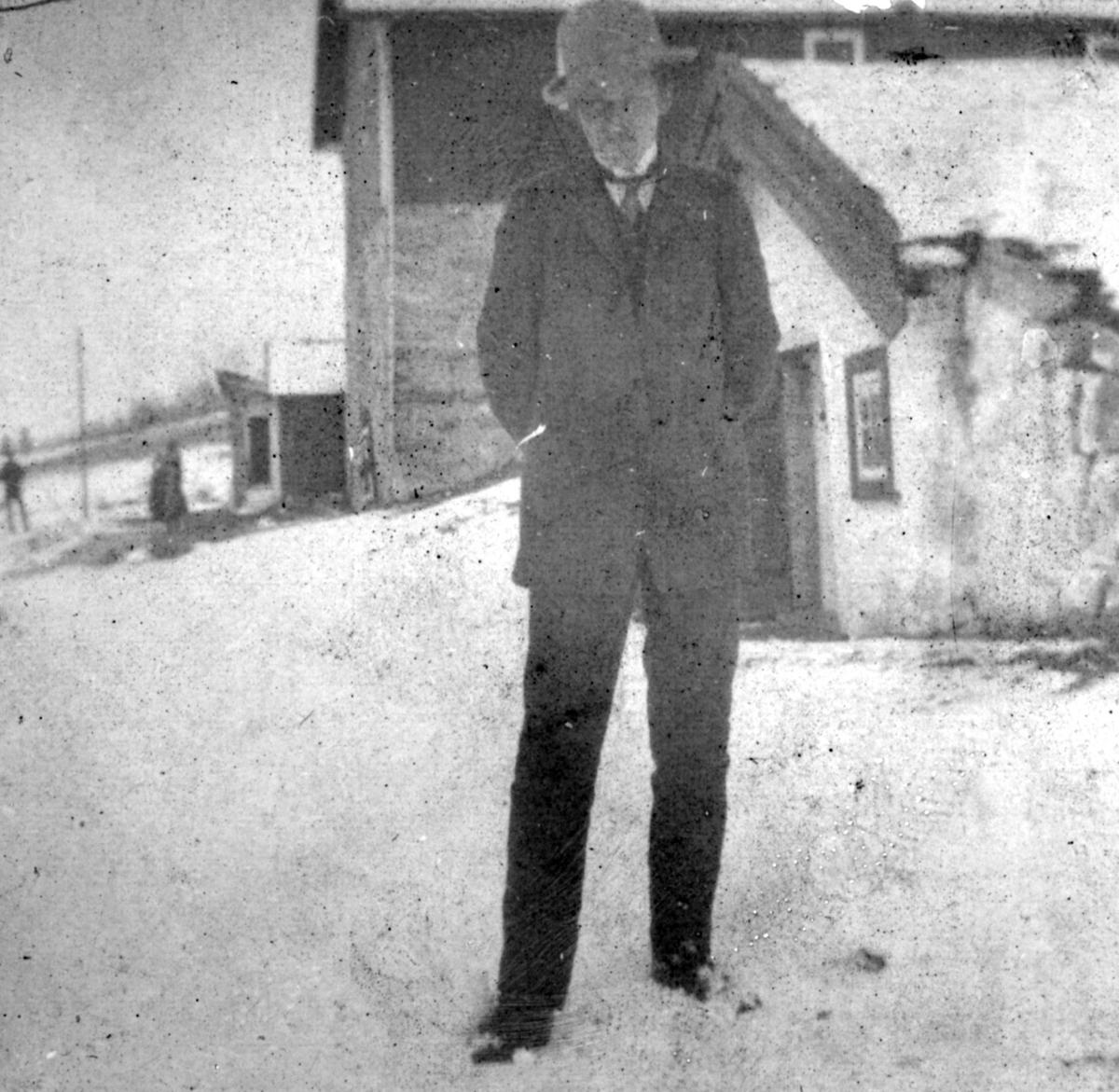 Johannes Büll-Hanssen står ute kledd i jakke, bukse og slips. På hodet har han en hatt. Bak han ligger det hus.
