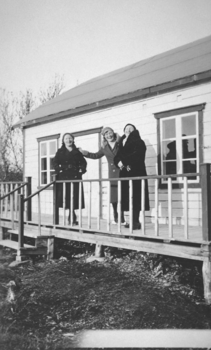 Tre kvinner står ute i kåper og luer. Kvinnen helt til venstre er trolig lærer Ragna Sofie Hansen.