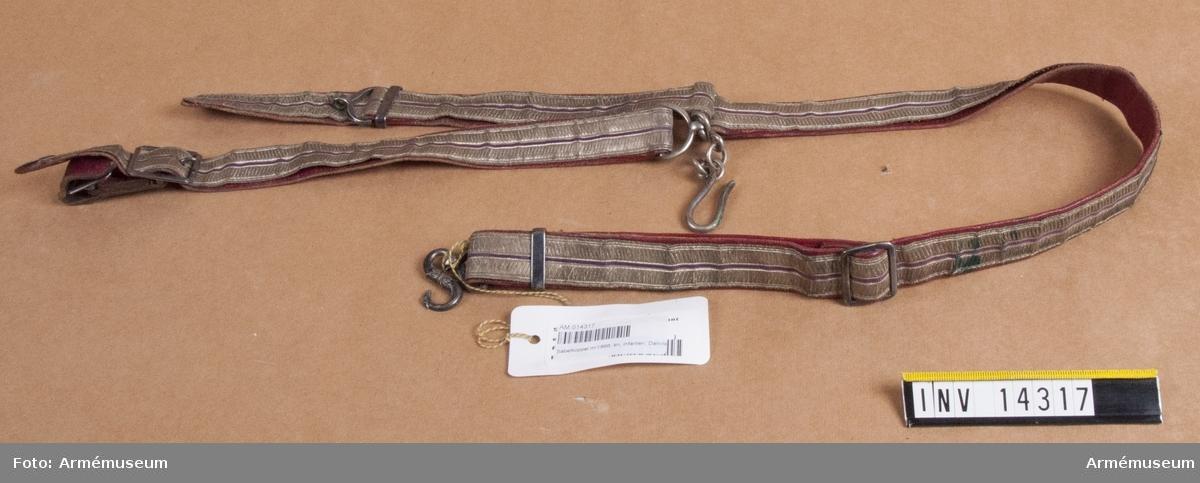 """Grupp C I. Sabelkoppel m/1868, 10 inf.bataljon, 7 inf.reg, Danmark.  Livrem av silvergalon, b: 25 mm, fodrad med rött skinn. Förgyllda spännen och beslag. Bärrem fastsydd vid livremmens ring. Ringen har kätting och hake för sabel. Släpremmen saknas.  Enl papperslapp från Töjhusmuseet tillhör detta koppel """"Fodfolk, Kaptajn: Gehaeng""""."""