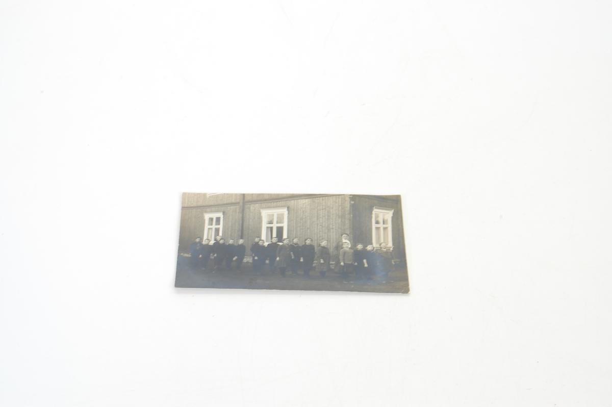 foto av mange barn og en voksen dame, et hus i bakgrunnen, sannaynligvis en skoleklasse