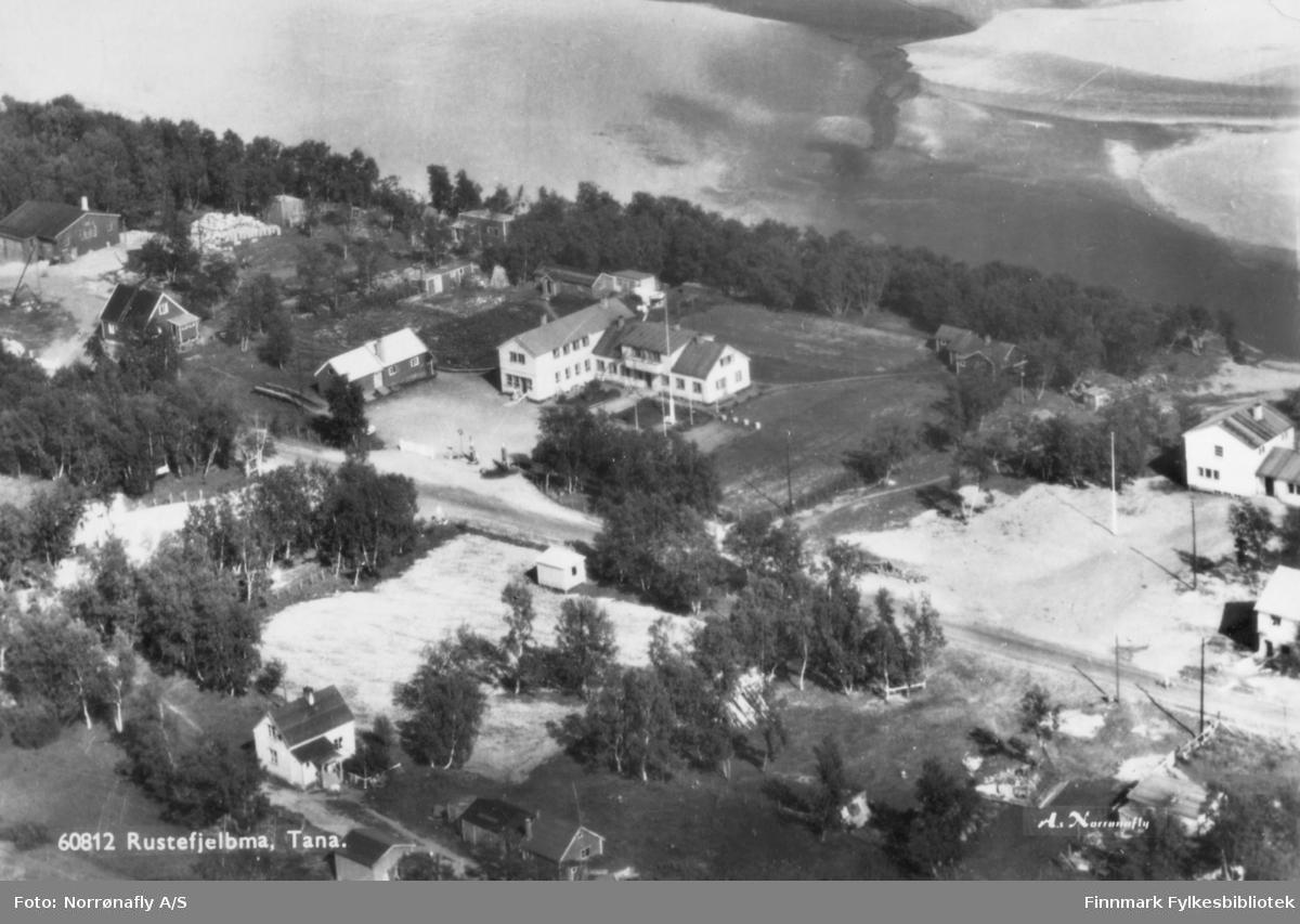 oversiktsbilde over Rustefjelbma, Tana. Bildet er et fotografi som senere et blitt laget om til et postkort. På bakken kan man se flere hus og bygninger blant trær og veier. Bildet er trolig tatt i løpet av siste halvdel av 1900-tallet.