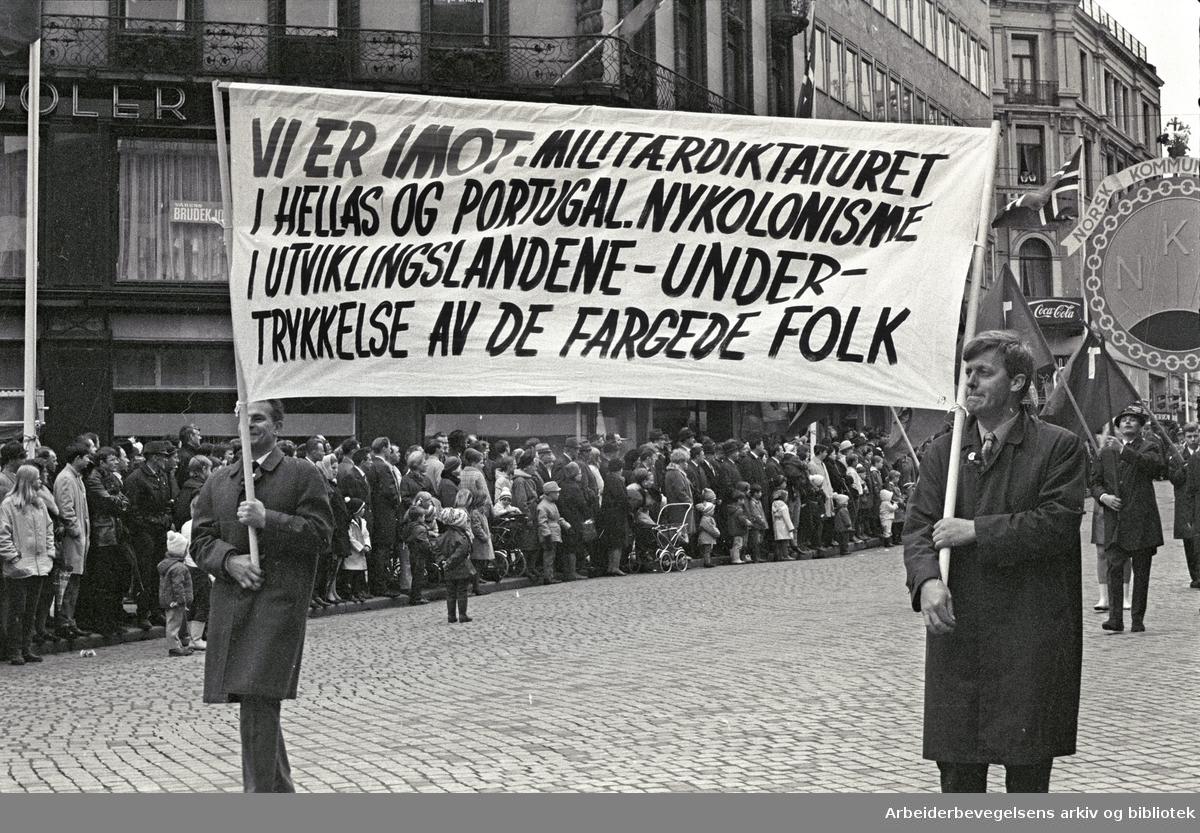 1. mai 1969 i Oslo.Demonstrasjonstoget i Karl Johans gate.Parole: Vi er i mot militærdiktaturet i Hellas og Portugal. Nykolonisme i utviklingslandene - .undertrykkelse av de fargede folk