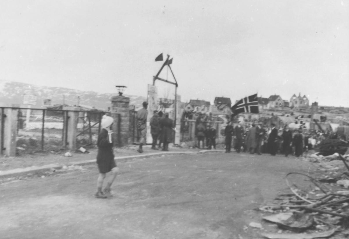 17.mai i Kirkenes, 1945. Tog med et par flagg. I forgrunnen et barn. I bakgrunnen boliger, delvis ødelagte.