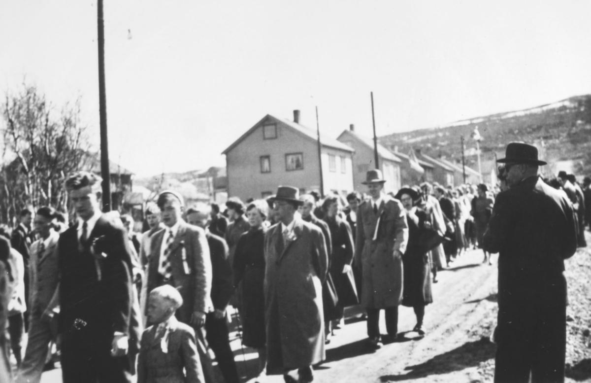 17.mai-tog i Kirkenes 1956. En mann filmer/fotograferer toget.