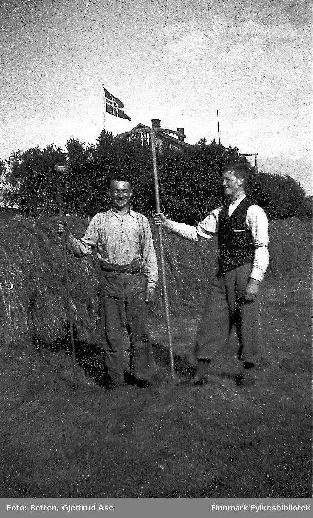 To menn, Isak og Einar, står på slotta med en ljo og en rake på hand. Høn er berget og hengt til tørk. Bakerst på bildet står et hus bak trår. Den norske flaggen er heist opp.