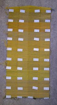 """Möbeltygsprover vävt i kypertvariation - med märketiketter. WLHF-998:1 - Provväv med varp av bomull i 4 olika nyanser beiget/brunt, uppdelat i 4 sektioner - benämnt A varp 454  - B varp 470 - C varp 462 - D varp 1224. Ett ca 1 cm brett parti  utan varp som gräns mellan varpsektionerna. Inslag av ullgarn och lingarn i olika nyanser av orange och gult i sammanlagt 10 olika partier benämnda """"Prov nr: A B C och D 1-10. Vid varje nytt provnummer finns en etikett och några trådar av inslagsgarnet. Mått: 990x420 mm. Bild A. Bild B visar en detalj.  WLHF-998:2 - Provväv remsa med samma gråbruna varp och 6 sektioner med olika nyanser på inslagsgarn, markerat med pappetikett Nr 1 - Nr 6, och några trådar av inslagsgarnet. Mått: 650x160 mm. Bilden är ett montage, visar provet t.h. och en närbild med Nr 5 t.v.Proverna utgör olika varianter av möbeltyg till St Persgården, Leksand, nybyggd 1988. Vävprov nr 5 hos 998:2 valdes att användas till stolar. Till proverna hör en Vävnota. Här står bl.a.: """"Gult melerat möbeltyg i korskypert till S:T Persgården  Varp: Bom.g 16/2 Inslag: 2 trådar Fårögarn (Gult & Guldorange) och 2 trådar lingarn 16/1 (Brun & Gul) Till varje stol vävdes 60 cm tyg. Totalt 60 st stolar"""". Vävnotan finns i """"LÅDA Tillbehör B"""", scannad till pärm och datamapp """"Tillbehör"""". Foton från 2007 som visar stolarna på plats samt stolsdyna tillsammans med provet :1 finns i datamappen """"Tillbehör""""."""