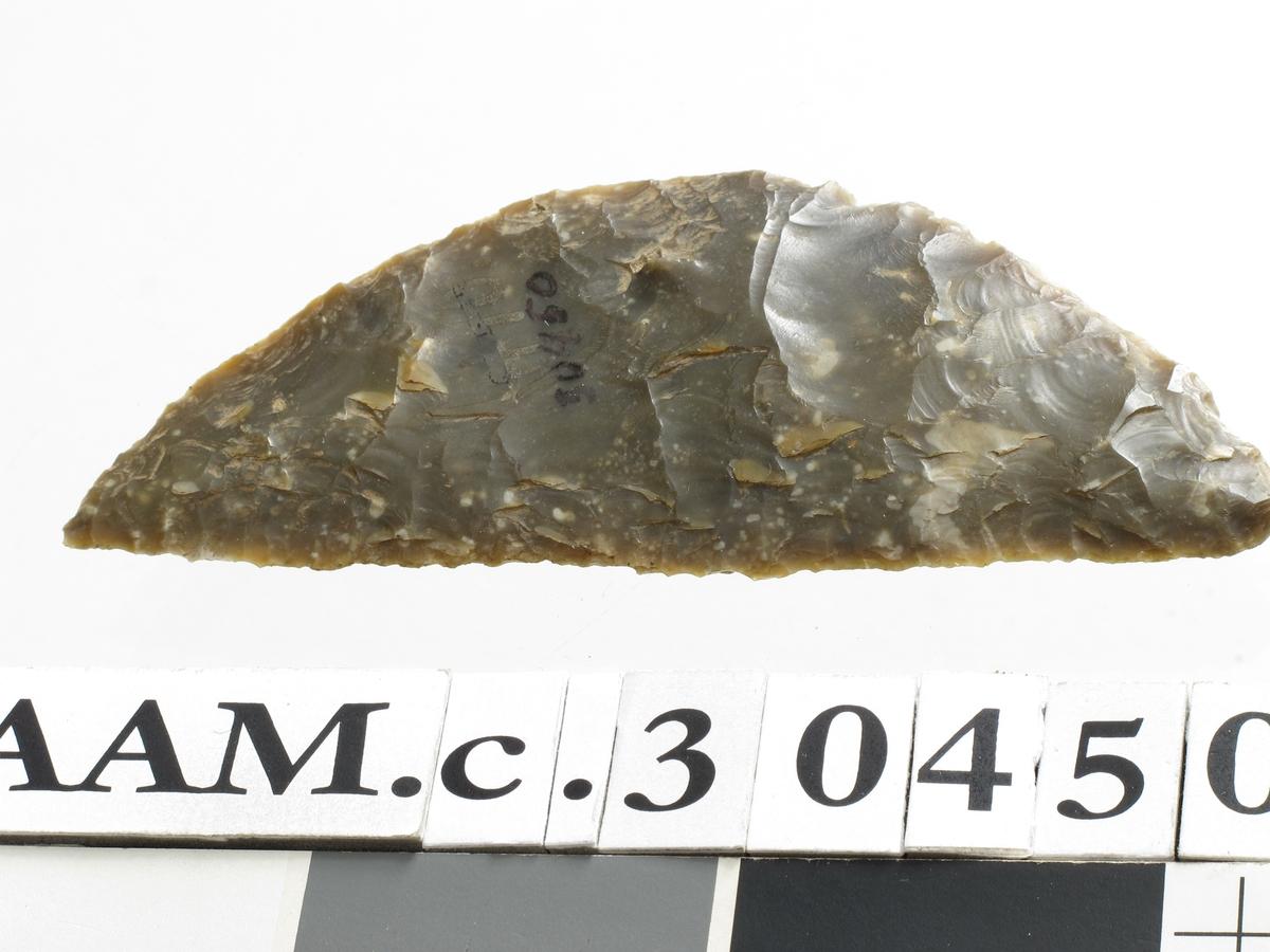 Sigd av mørk brunlig spettet flint av typen H. Gjessing: Rogalands Stenalder, fig. 235, men lengre og mindre bred. Godt hugget og bevart. Eggen har den karakteristiske blanke overflaten, som tyder på at stykket er brukt til skjæring av korn.