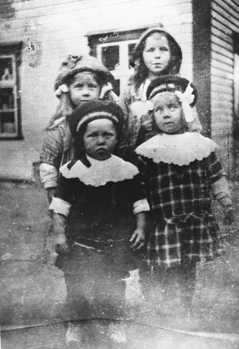 Portrett av 3 jenter og en gutt foran 'Husby - hjørnet'. To vinduer på husveggen. Fra venstre er Ruth med hatt og bånd i håret på begge sider. Ved siden er Ester Lein som har sydvestlignende hatt. Foran er Odd Killi i mørk dress med hvit blondekrage og armene oppbrettet.Han har matroslue på.Ved siden Lilly Lein i rutet kjole med hvit blondekrage og matroslue.