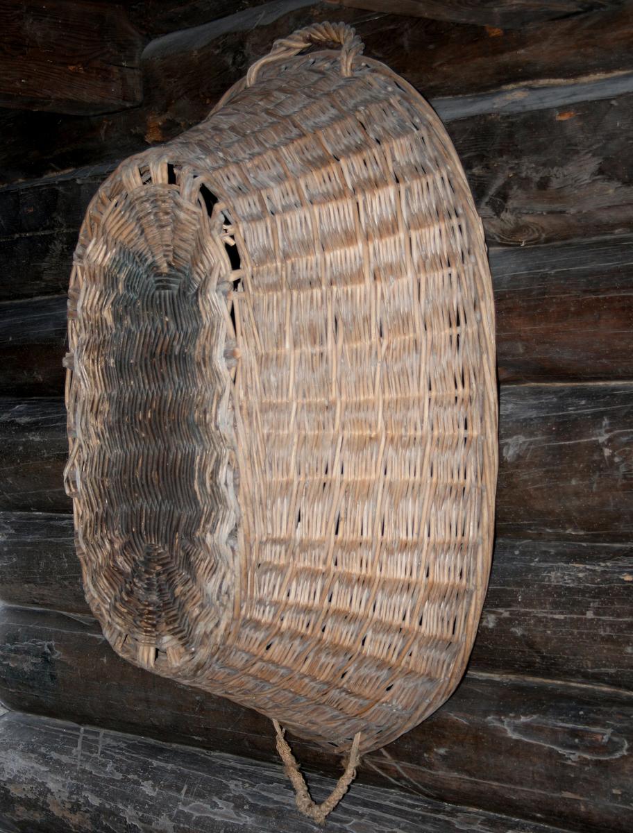 Flisekurv henger på veggen i bryggerhuset.  Svær oval kurv av baljeform med oppoverskrånende sider, av grove teger.  Tre.  Rundflettet bunn, flettet hank og tauhank.