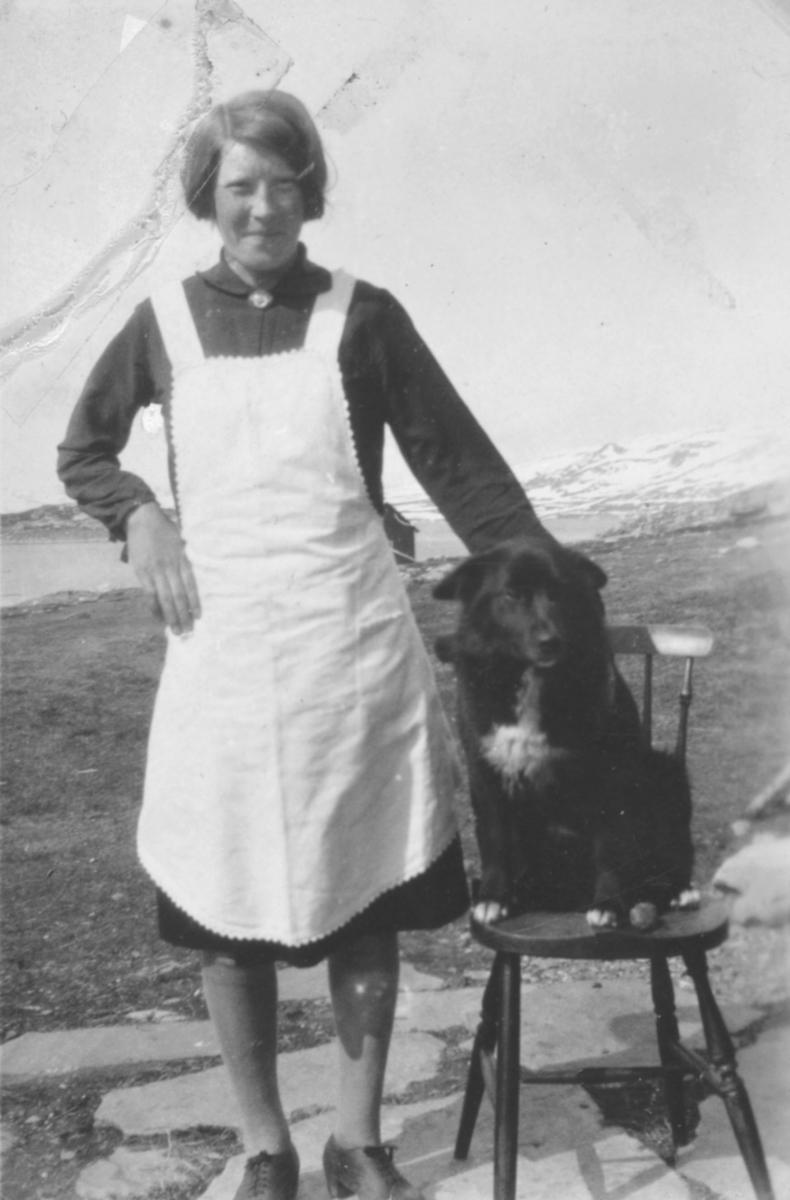 En ung dame fotografert sammen med en hund. Sted og person er ukjent, men bildet kan være tatt i Kvalsund kommune.
