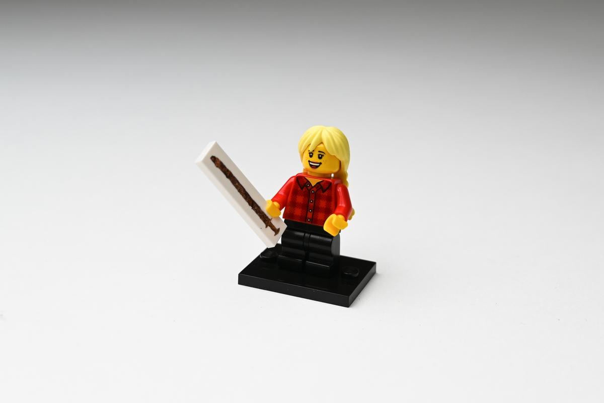 Legofigur av plast föreställande en flicka som håller upp ett svärd i ena handen. Flickan har gult hår i två flätor på ryggen, är klädd i röd- och svartrutig skjorta och svarta byxor. Figuren står på en svart platta. På en vit avlång platta, som figuren håller i handen, finns en bild av svärdsfyndet från Tånnö socken, Jönköpings län. Se vidare Historik.  Figuren förvärvades i en liten plastpåse med fasthäftad pappersetikett.