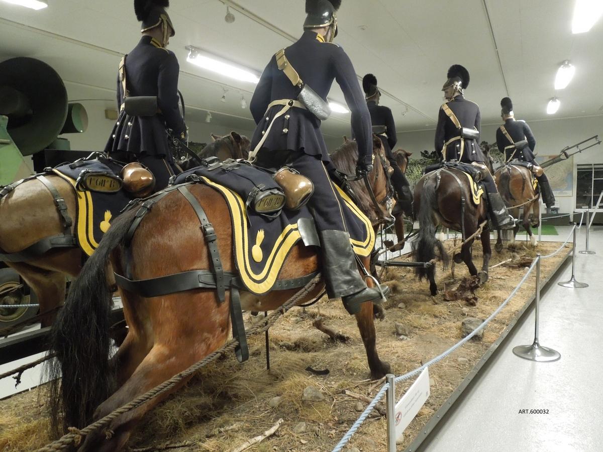 """6-spann för artilleriet i helformat   På museet finns ett komplett spann för 6-pundig kanon m/1832 dragen av 6 hästar från Wendes ridande artilleri 1850.  Wendes är f d artilleriregementet A3 i Kristianstad. Ett föremål av högsta klass framställt i helformat. Ansvarig är Auktoriserade Zoologiska Konservatorn Jeanette Setterberg, Framtaget i slutet av 1990-talet och invigt 2000 på Armémuseum. Förstudier, film/foto skedde på Artillerimuseet i mitten av 1990-talet då museet hade två spann i drift (senare ett spann och fortfarande 2020) för att få rätt rörelseschema för hästar som drar en kanon i galopp. Gåva från Armémuseum till Artillerimuseet 2013. Något ur arbetsbeskrivningen: Konservatorn anskaffade passande hästar, f d privata, från Uddevalla- och Karlstad-trakten. Svårt att stoppa upp en häst. Här valdes att först gjuta """"hästarna"""" av plast för att sedan """"klä """"dessa med de riktiga hästarnas skinn. En bild från konservatorn ger underlag. På detta sätt blev resultatet ett helt världsunikt """"levande """" 6-spann. Gubbarna, komplett utrustade, är också med levande bakgrund från konservatorns arbetskamrater."""
