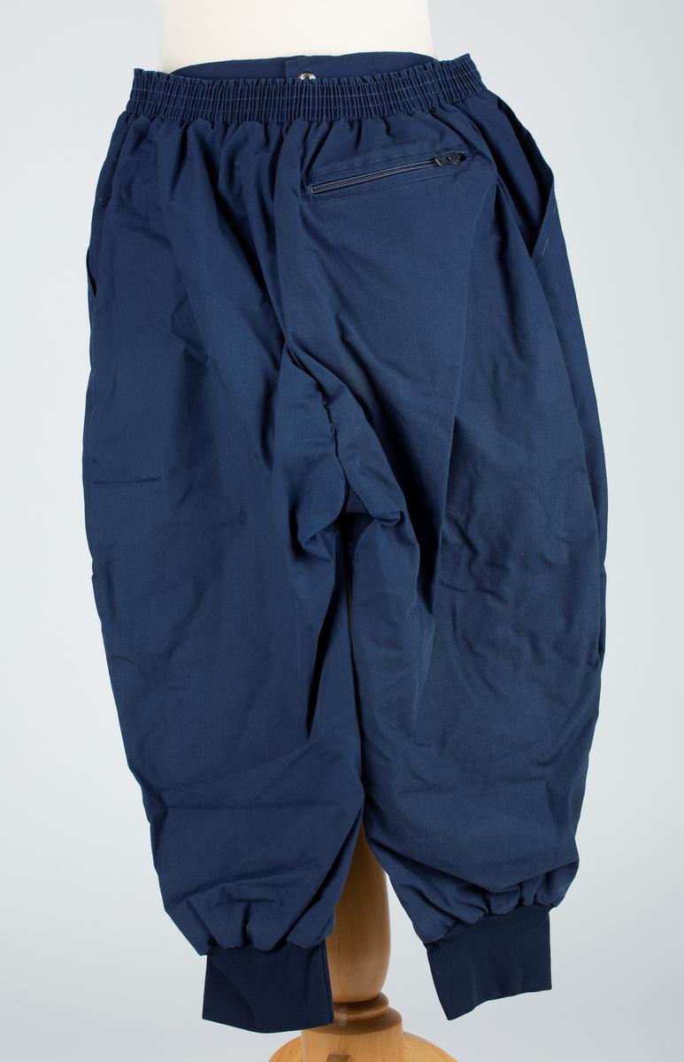 """Nikkers,  i mørkeblå bomull, rødt trikot for. Løpegang med strikk i livet. Krepp mansjett ved kneet. Glidelås i gylf., trykknapp. Baklomme.  Str.44. Mrk:""""Odlo Sportswear"""". fra Odlo fabrikker i Oppegård. God tilstand."""