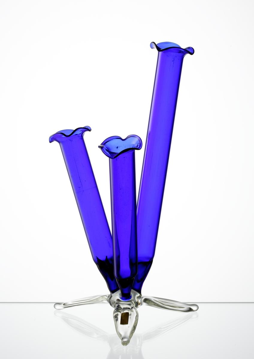 """Blå vas, med tre separata behållare för styckeblommor eller mindre buketter, i form av en blomma med tre blad som fot.  Etikett """"HANDARBETE R. EKOFF"""""""