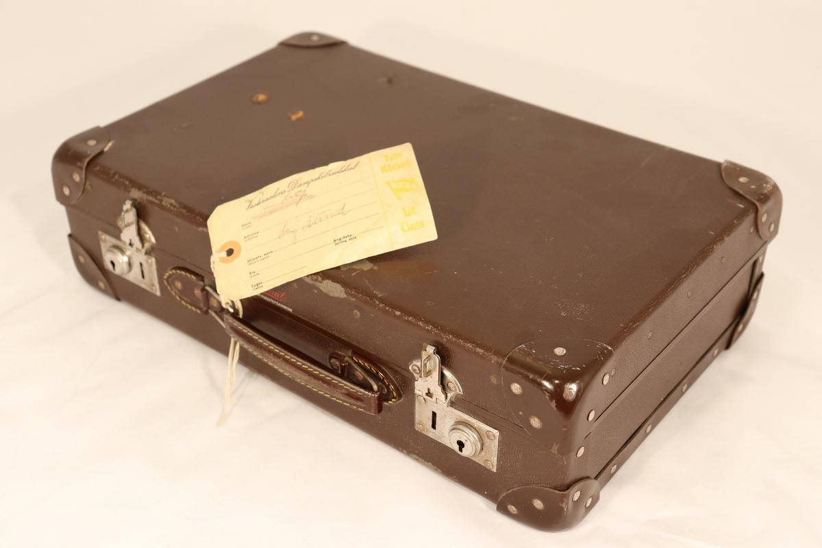 Til kofferten er det knyttet en merkelapp (reisegods) - Vesteraalens Dampskibsselskab.