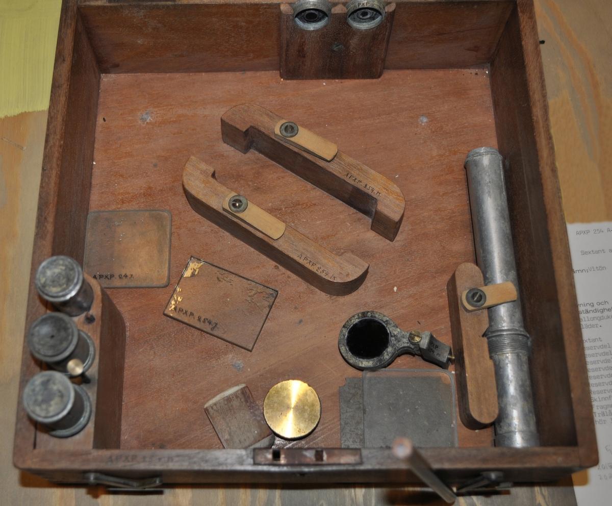 Sextant av aluminium i låda av trä.  A. Sextant B. Reservdel, tubformad C. Reservdel, tubformad D. Reservdel, tubformad E. Reservdel, tubformad, längre F. Reservdel G. Reservdel med glas H. Reservdel med tre svarta glas I. Skinnfodral till föregående J. Fragment av spegelglas K. Trälåda (fem lösa träbitar och en lös metalldel tillhör lådan samt 2 gångjärn. Liten metallbit som är märkt APXP 254