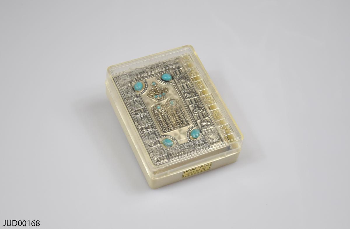 """Bönbok med omslag i typisk Betsalelstil, tillverkat av silver. Omslaget visar stentavlorna med de tio buden och en torakrona med infattade turkoser.  Runtomkring står de tolv stammarnas namn och deras symboler. På baksidan ser man den sjuarmade ljusstaken menorah, och samma citat från Jesaja som på framsidan: """"Ty från Sion ska Toran utgå""""."""