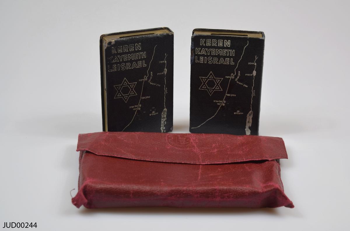 Två stycken insamlingsbössor utformade som böcker, tillverkade av mässing. Silvrig dekor i form av Davidsstjärna, karta över Israel samt hebreisk text. Även dekorerad med följande text: Keren Kayemeth Leisrael JNF Jerusalem
