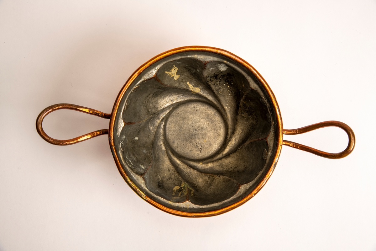 Puddingform av kobber,  innv. fortinnet.  Dyp skålformet med svungne sider, to lange utstående hanker.