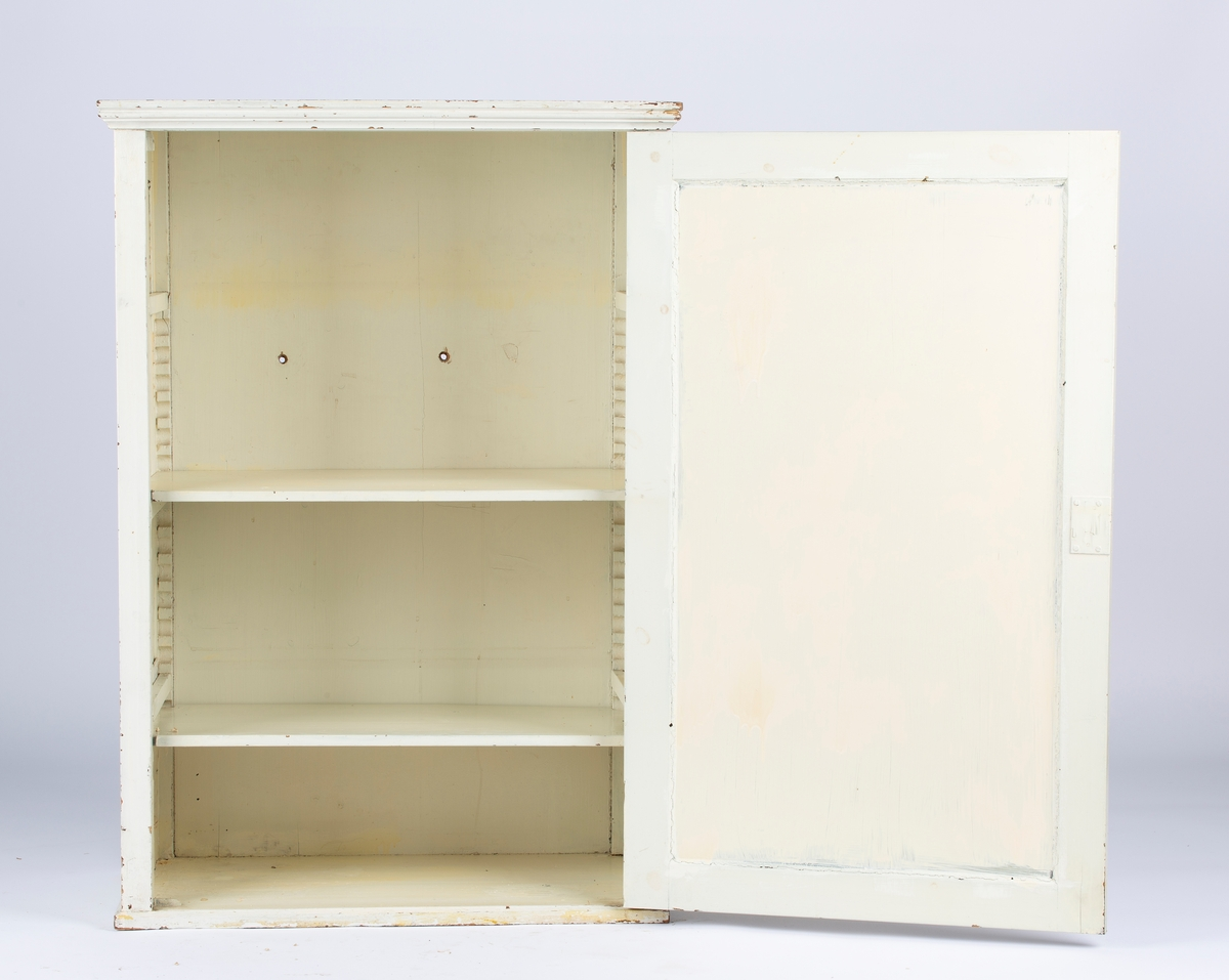 Rektangulært skap med en dør og to løse hyller hyller. Overmalt glass i dør og sider. I skapets høyre side, sett forfra, er det satt inn to plater som overlapper hverandre hverandre. Platene er overmalt slik som glasset. Det følger med en nøkkel til skapet, låsen i døren er montert opp ned. Det ser ut som om noe kan ha vært plassert på toppen av skapet, da bare halv toppen er malt flere ganger. Ca. 32 cm opp fra gulvnivå og med 20 cm avstand er det to hull gjennom skapets bakvegg.  Fra baksiden av skapet kan man se et hull til, men det er tettet fra innsiden.
