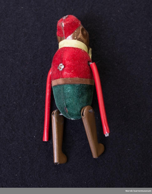 Apekatt som kan trekkes opp. Har på seg røde og grønne klær. Blir oppbevart i en rød eske.
