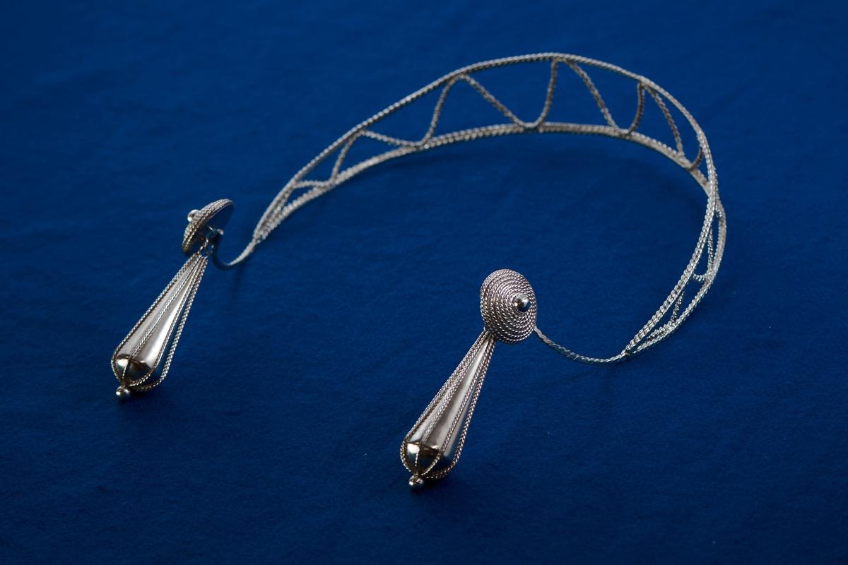 Silversmycke i filigranteknik av Rosa Taikon. Tunga, droppformade örhängen är vanliga smycken hos flera romska grupper. De kan vara utförda i såväl solid som genombruten form. Ofta bärs tyngden upp av en tunn kedja som läggs runt örat för att avlasta örsnibben. I det här huvudsmycket har Taikon valt att istället låta tyngen bäras av huvudet genom att fästa hängena i ett diadem av filigran.