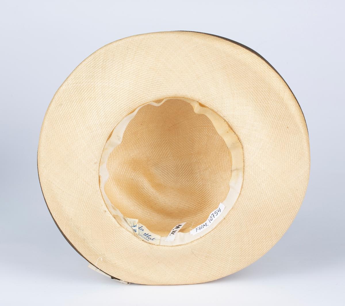 Rund hattepull, vid brem kantet med brunt ripsbåndhattebånd. Rundt hodepullen bredt ripsvevet , lyst hattebånd med sløyfe bak.
