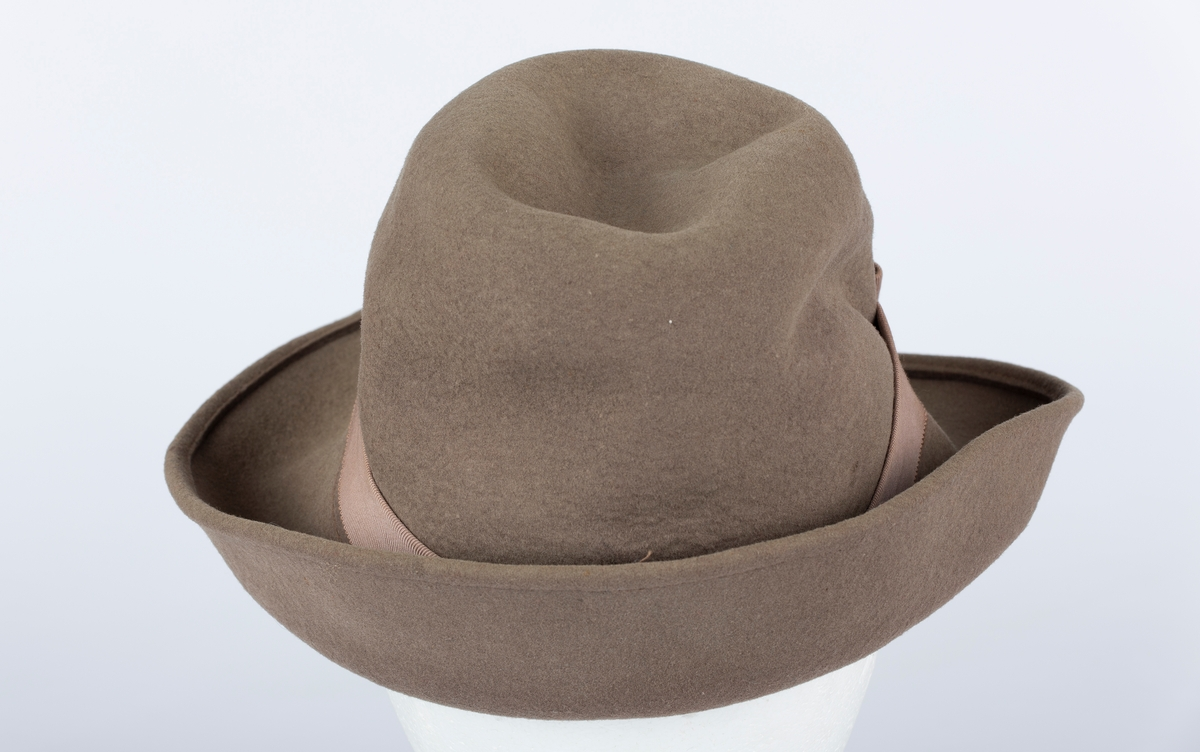 Hatt. Rund hattepull med brem. Bremmen brettet opp. Ripsbånd med sløyfe rundt hattepullen.