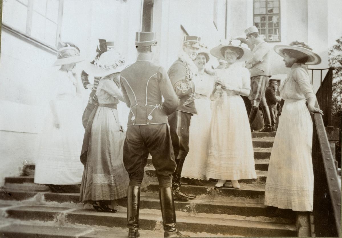 Sällskap med kvinnor och soldater på trappuppgång.