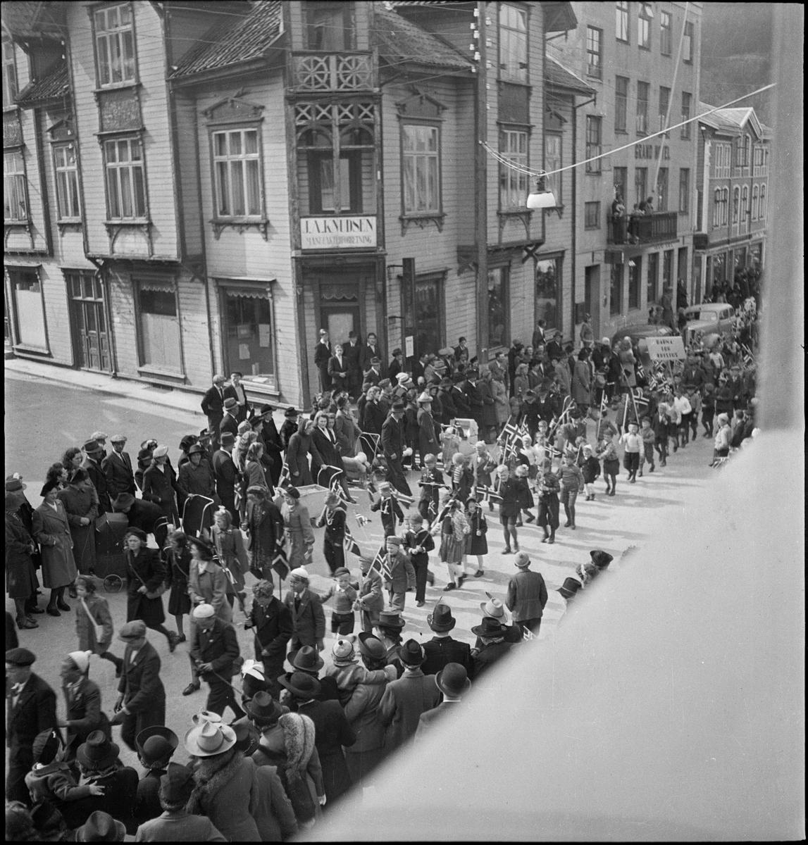 """Barnetog og musikkorps går igjennom sentrum av Egersund i anledning søndagsskolens dag. Flere bærer norske flagg og et barn bærer en plakat med teksten """"Jesus er barnas venn""""."""