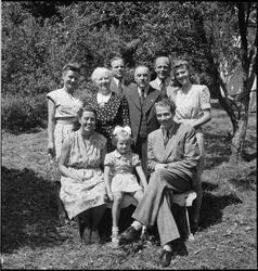 Familien Zakariassen i hagen og i ei stue. Det er en eldre m