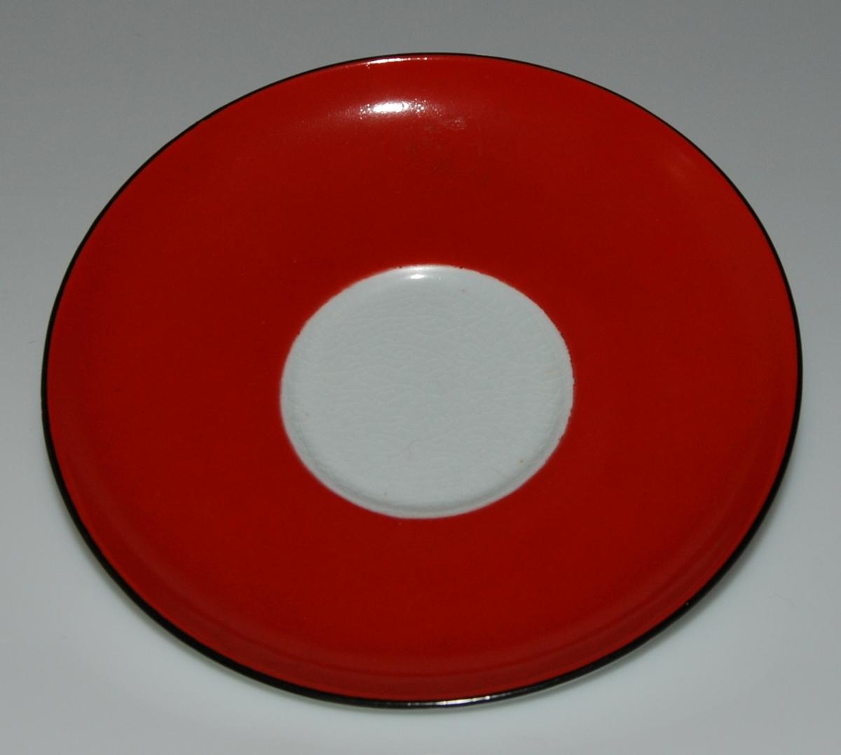 Tekopp med fat, röd med vita prickar.